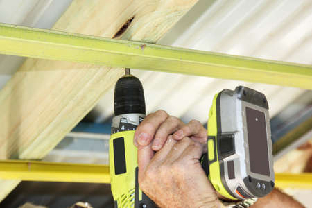 ceiling construction: a cordless hand drill used to put ceiling battens Stock Photo