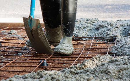 hormigon: persona con botas de goma en el trabajo en la difusión de concreto premezclado