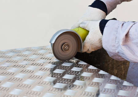 cutting metal: handyman cutting metal plate with safety gear on Stock Photo