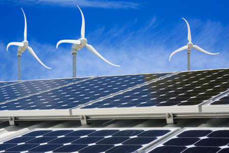 photocell: solar panel on a house with wind generators in background Stock Photo