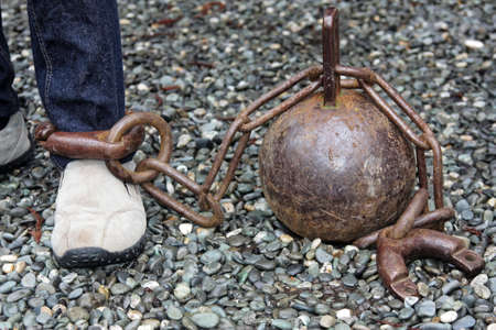 chain ball: large ball and strong chain on leg Stock Photo