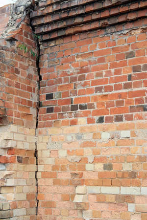 bricks background: Close-up view of cracked old building brick wall with eroded bricks on top, background concept