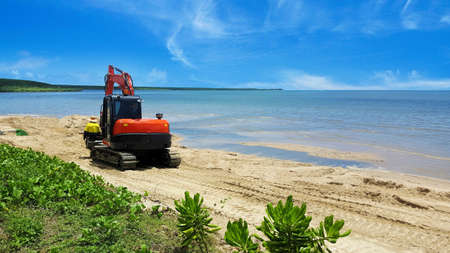Excavator or digger moving beach sand after erosion by the tides on a tropical beach with calm ocean in Cairns, Queensland, Australia Stock Photo