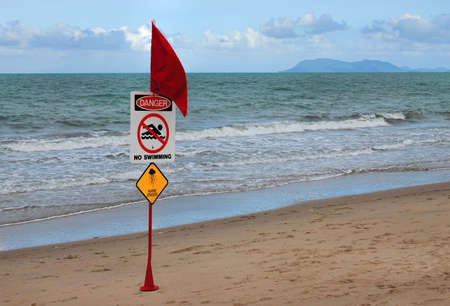 Red warning flag on beach with Danger No Swimming sign and jellyfish image. Highlighted colored flagpole against  tropical costal landscape