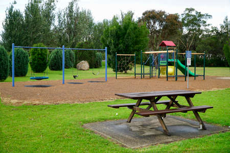 Parque infantil con banco de parque de madera en primer plano