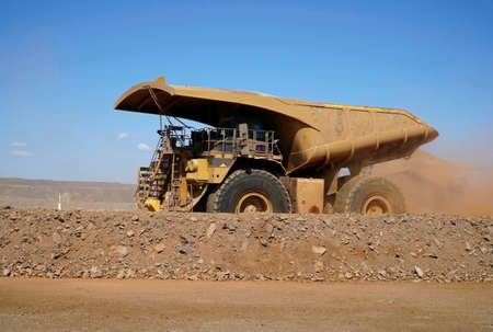 Gold mine operation in a open gold mine pit with large haul truck leaving with dirt