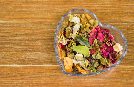 glass bowl: Colorful Dried Flowers in Heart Glass Bowl Stock Photo