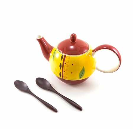 yellow tea pot: Isolated Yellow Ceramic Tea Pot with Two Wooden Spoons on White Background Stock Photo