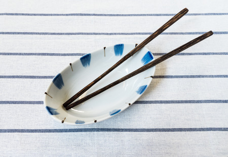 noodle bowl: Chinese Noodle Soup Bowl with Wooden Chopsticks on Striped Fabric