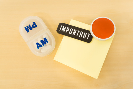 important reminder: Reminder Pill Box with Important Word and Big Red Smile on Yellow paper Placed on Table Surface