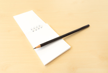 sharp pencil: White Memo Note with Black Sharp Pencil on Wooden Surface