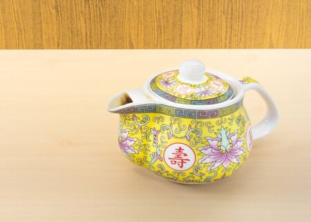 yellow tea pot: Chinese Yellow Tea Pot with Art Pattern Placed on Wooden Surface Stock Photo