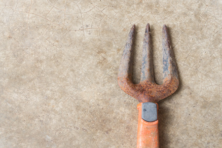 replant: Rusty Old Fork Gardening Tool on Concrete Floor Background Stock Photo