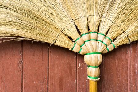 wicker work: Broom Stick Lay on a Brown Wooden Door