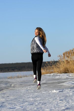 The girl in the early spring, snow melts, the sun warms photo
