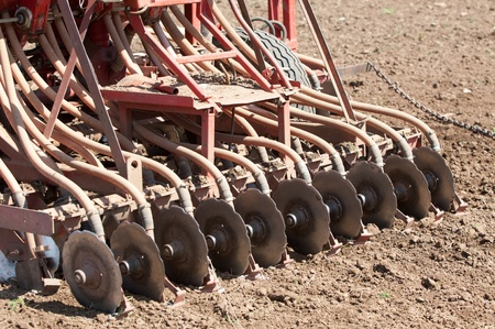 Tractor in the field. Tractor at the seed. Tractor working on the field. Tractor sowing seed. Ploughing heavy tractor during cultivation agriculture works at field with plough