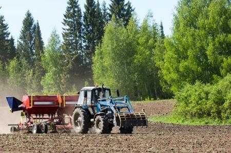 Tractor op het gebied Tractor op het zaad Tractor werken op het veld Tractor zaaigoed Ploegen zware trekker tijdens de teelt landbouw werkt op veld met ploeg