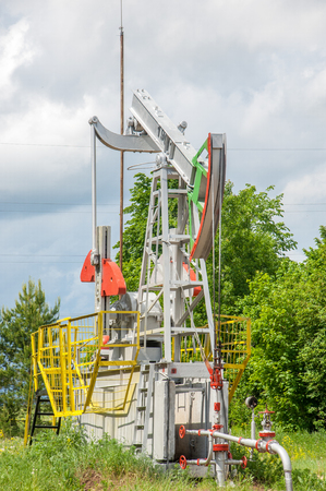 oney: Oil and gas industry. Work of oil pump jack on a oil field. White clouds and blue sky. oil well pump. Oil and gas industry. Work of oil pump jack on a oil field.