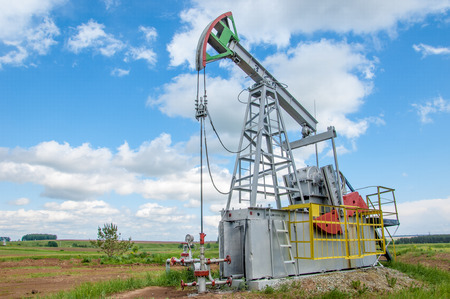 nodding: Oil and gas industry. Work of oil pump jack on a oil field. White clouds and blue sky. oil well pump. Oil and gas industry. Work of oil pump jack on a oil field.
