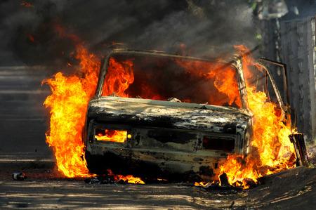 Lieferung Typ Fahrzeug auf Seite der Straße mit großen brennenden Flammen und Rauch. Autobrand auf Wüstenlandstraße. Auto in Brand und Unfall nach oder während eines Aufstands. Standard-Bild