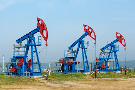 Oil and gas industry. Work of oil pump jack on a oil field. White clouds and blue sky. oil well pump. Oil and gas industry. Work of oil pump jack on a oil field. Stock Photo - 31724710