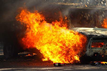 Delivery type vehicle on side of road burning with large flames and smoke. Car fire on desert rural road. Car on fire after and accident or during a riot.