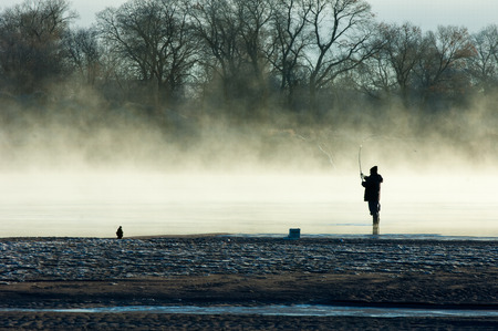 fishermen. A fisherman fight against a bass at sunset. Fisherman silhouette on the beach at colorful sunset. Fly fisherman walking beautiful landscape photo