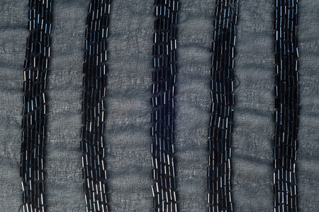smutty: Fabric Color black with beads.  Photography Studio. texture. ebon, sable, smutty. of the very darkest color owing to the absence of or complete absorption of light; the opposite of white