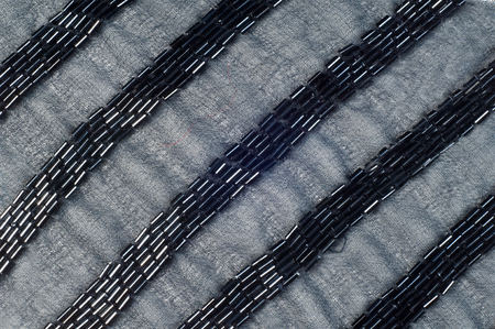 ebon: Fabric Color black with beads.  Photography Studio. texture. ebon, sable, smutty. of the very darkest color owing to the absence of or complete absorption of light; the opposite of white