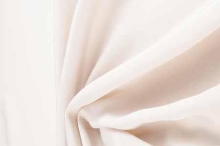 lustrous: Fabric silk texture, cream, cream-colored, cream-coloured, pale beige. a fine, strong, soft, lustrous fiber produced by silkworms in making cocoons and collected to make thread and fabric. Stock Photo