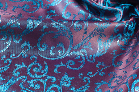 lustrous: Fabric silk texture blue, flowers, abstract. a fine, strong, soft, lustrous fiber produced by silkworms in making cocoons and collected to make thread and fabric.