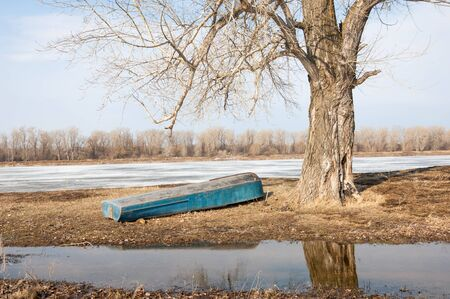 winter thaw: Spring River, the ice on the river. picturesque spring landscape with river ice melted bare trees and beautiful clouds in the blue sky