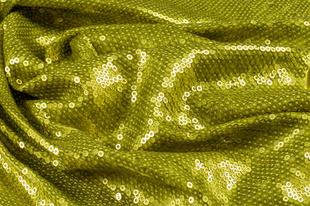 sewn: Fabric texture with green sequins. a small, shiny disk sewn as one of many onto clothing for decoration Stock Photo