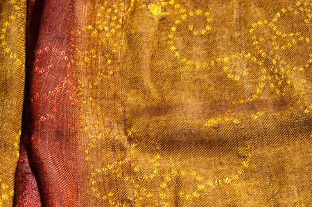 The texture of wool fabric yellow red golden. Womens scarf, the perfect backdrop.  cravat, neckerchief, kerchief, muffler, throw. a length or square of fabric worn around the neck or head. Stock Photo