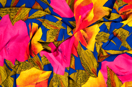 The texture of the silk fabric, red and yellow flowers on a blue background photo