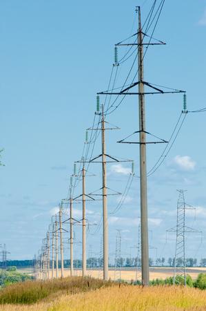 torres de alta tension: Fila de numerosos de alta tensión, torres industriales de alta resistencia para la distribución de la electricidad.