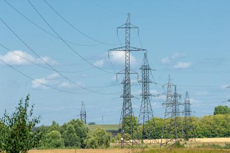 electricidad industrial: Fila de numerosos de alta tensión, torres industriales de alta resistencia para la distribución de la electricidad.