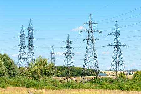 torres el�ctricas: Fila de numerosos de alta tensi�n, torres industriales de alta resistencia para la distribuci�n de la electricidad.