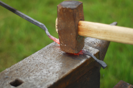 forger: blacksmith, smith, farrier, hammersmith, forger, smithy. treat (metal) by heating, hammering, and forging it. Stock Photo