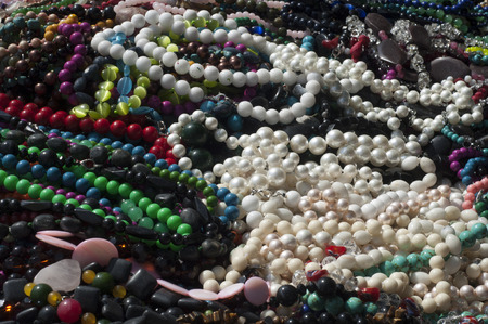 threading: bead, chaplet, beading. a small piece of glass, stone, or similar material, typically rounded and perforated for threading with others as a necklace Stock Photo