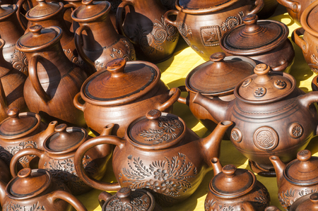 pottery, earthenware, clayware, crockery, stoneware. a large container, typically earthenware,  with a handle and a lip, used for holding and pouring liquids.
