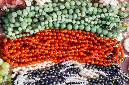 chaplet: bead, chaplet, beading. a small piece of glass, stone, or similar material, typically rounded and perforated for threading with others as a necklace Stock Photo