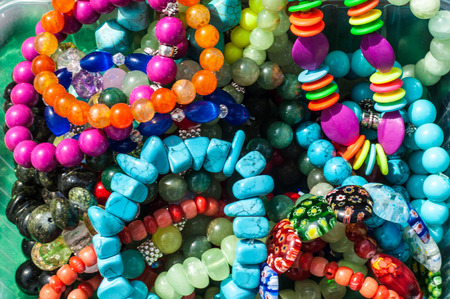 beading: bead, chaplet, beading. Texture, background. a small piece of glass, stone, or similar material, typically rounded and perforated for threading with others as a necklace or rosary or for sewing onto fabric.