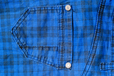 levi: texture of denim products. background. Indigo color with bright buttons. Pair of blue jeans.
