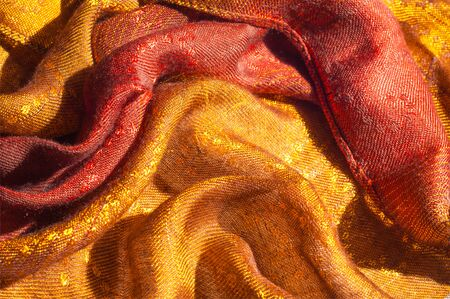 neckerchief: The texture of wool fabric yellow red golden. Womens scarf, the perfect backdrop.  cravat, neckerchief, kerchief, muffler, throw. a length or square of fabric worn around the neck or head. Stock Photo