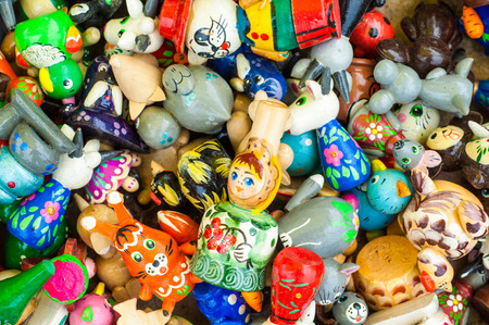 forcing: Background. Texture. Small earthenware toys, Painted colors. whistle a clear, high-pitched sound made by forcing breath through a small hole between partly closed lips