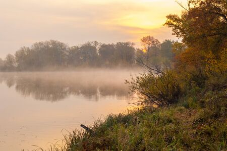 fall trees: Landscape. Sunset over the lake, fall trees reflected in water.  fog, mist, haze, smoke, brume, toman Stock Photo