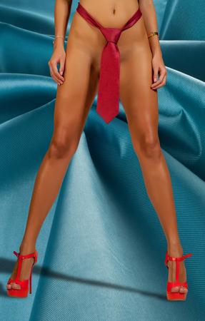 jeune femme nue: Gros plan d'un torse de femme nue, ses parties intimes ne sont pas visibles, femme vêtue de la cravate de l'homme. ventre fille. les jambes de la jeune fille. Des chaussures rouges. XXX. jambes féminines parfaites porter des talons hauts.
