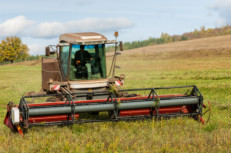 grass cutting: Autumn meadow for mowing grass. harvester for mowing grass.  Agricultural image of a large mechanized Swather mowing a grass field to make quality grass hay bales for livestock feed
