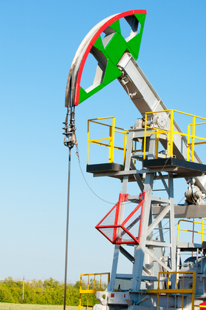 chink: Oil rocking chair closeup. Oil rocking chair on a background of blue sky. The pumping unit as the oil pump installed on a well. Equipment of oil fields. Stock Photo